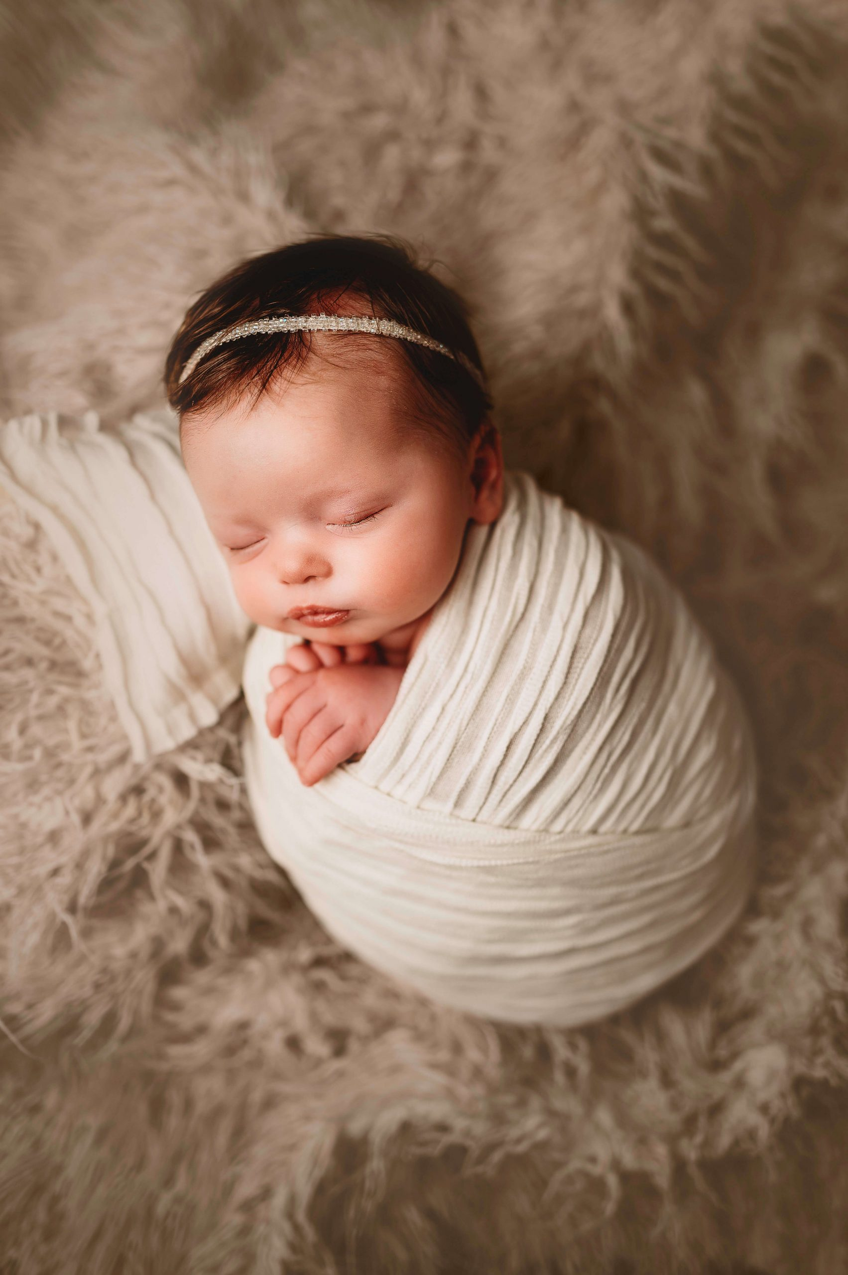 baby girl wrapped posed on pillow
